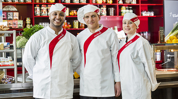 Three sodexo chefs standing in front of a counter