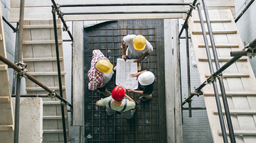 Four adults in a construction site wearing hard hats and looking at building plans, photographed from above