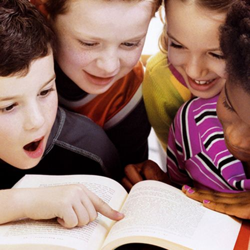 four children reading a book together